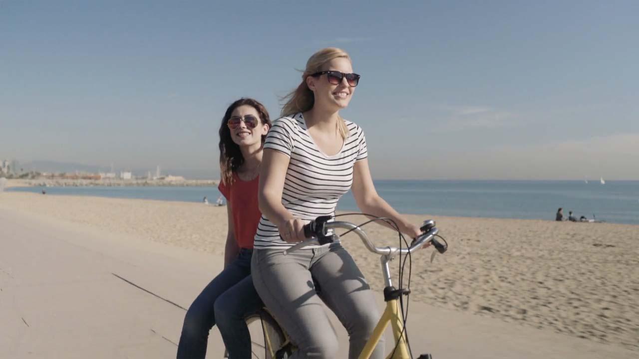 2 girls biking on the beach