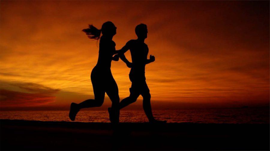 Couple running against sunset backdrop